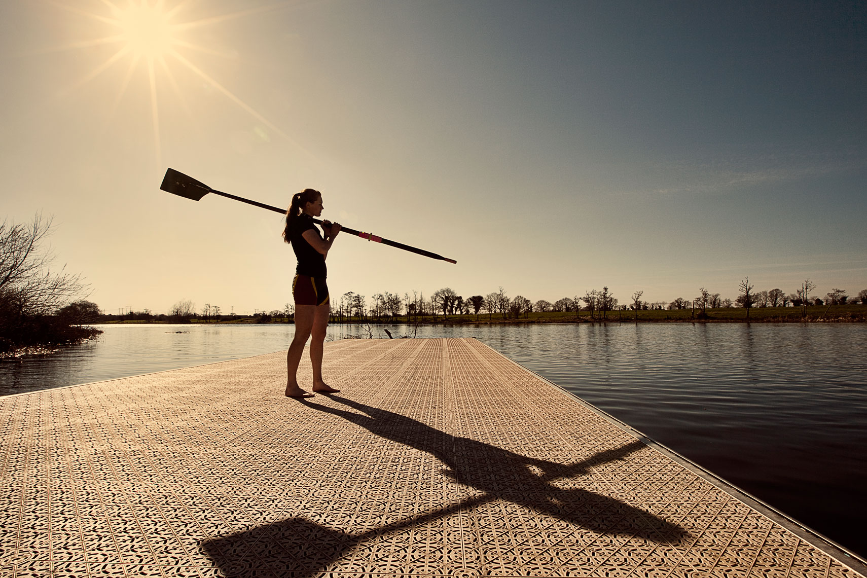 female rower stands on jetty during sunset