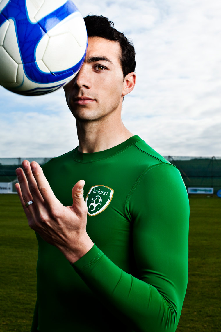 professional footballer wearing Ireland jersey throws ball