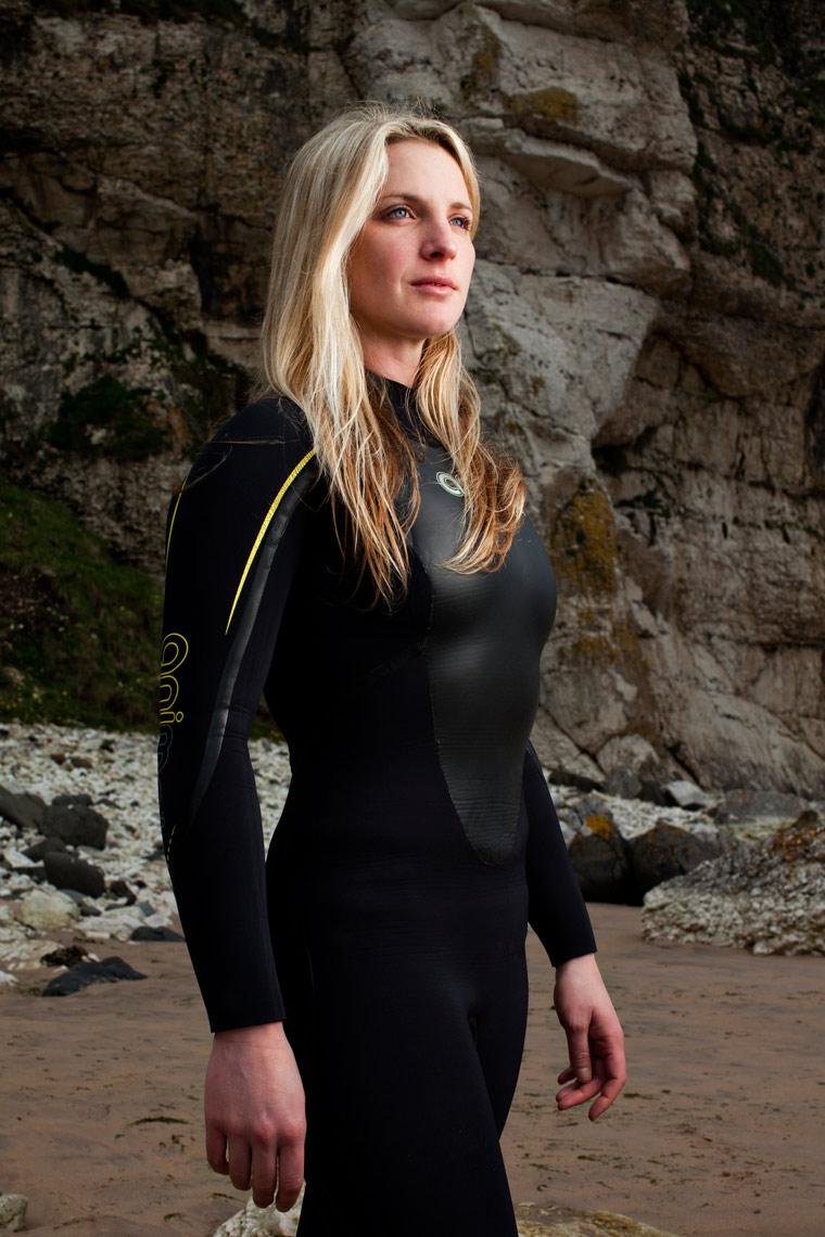 female surfer with long blond hair stands in black wetsuit