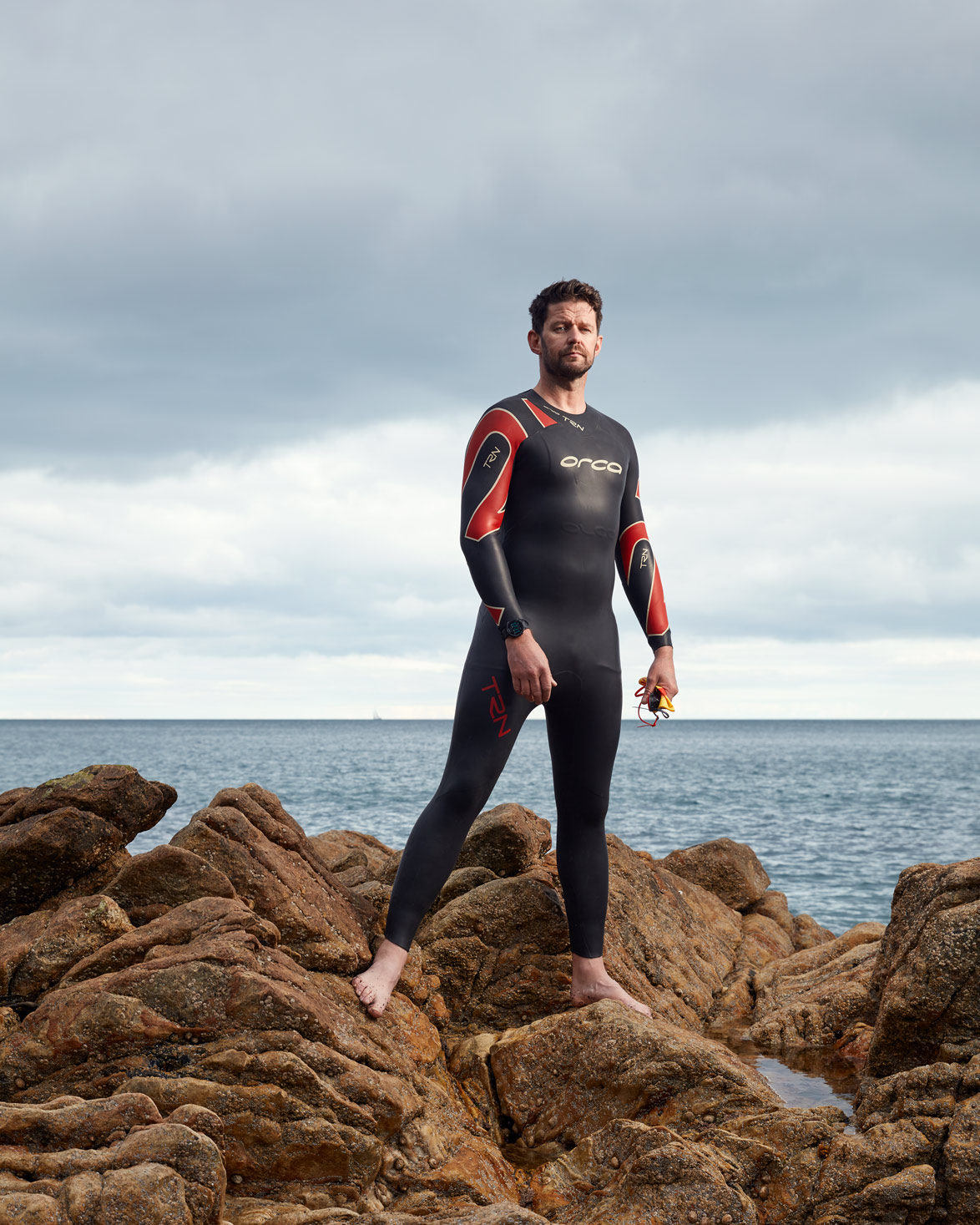 business photography: triathlete standing on rock