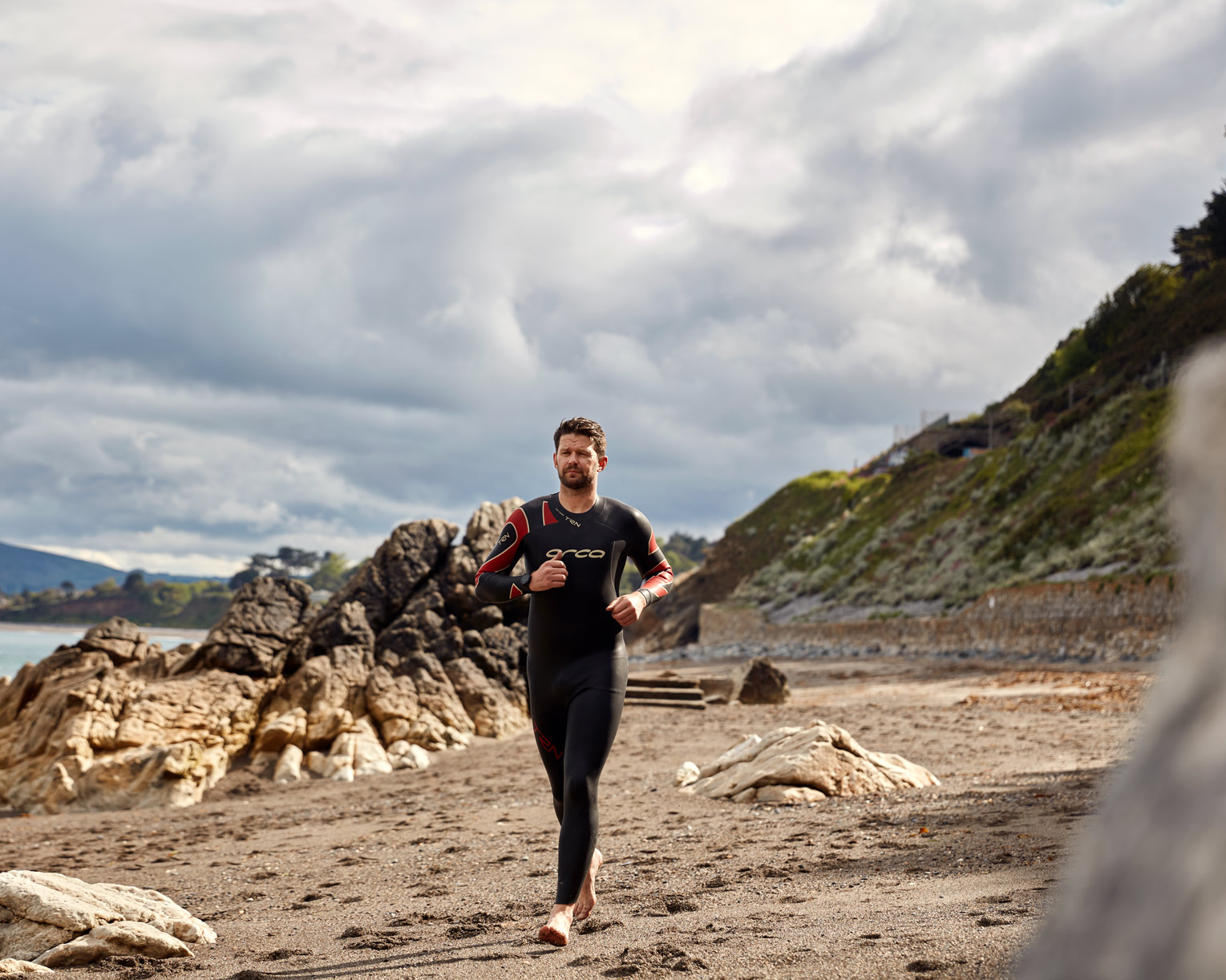 triathlete running in wetsuit sports photographer
