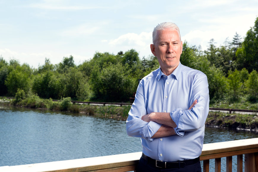 ceo stands beside lake for portrait
