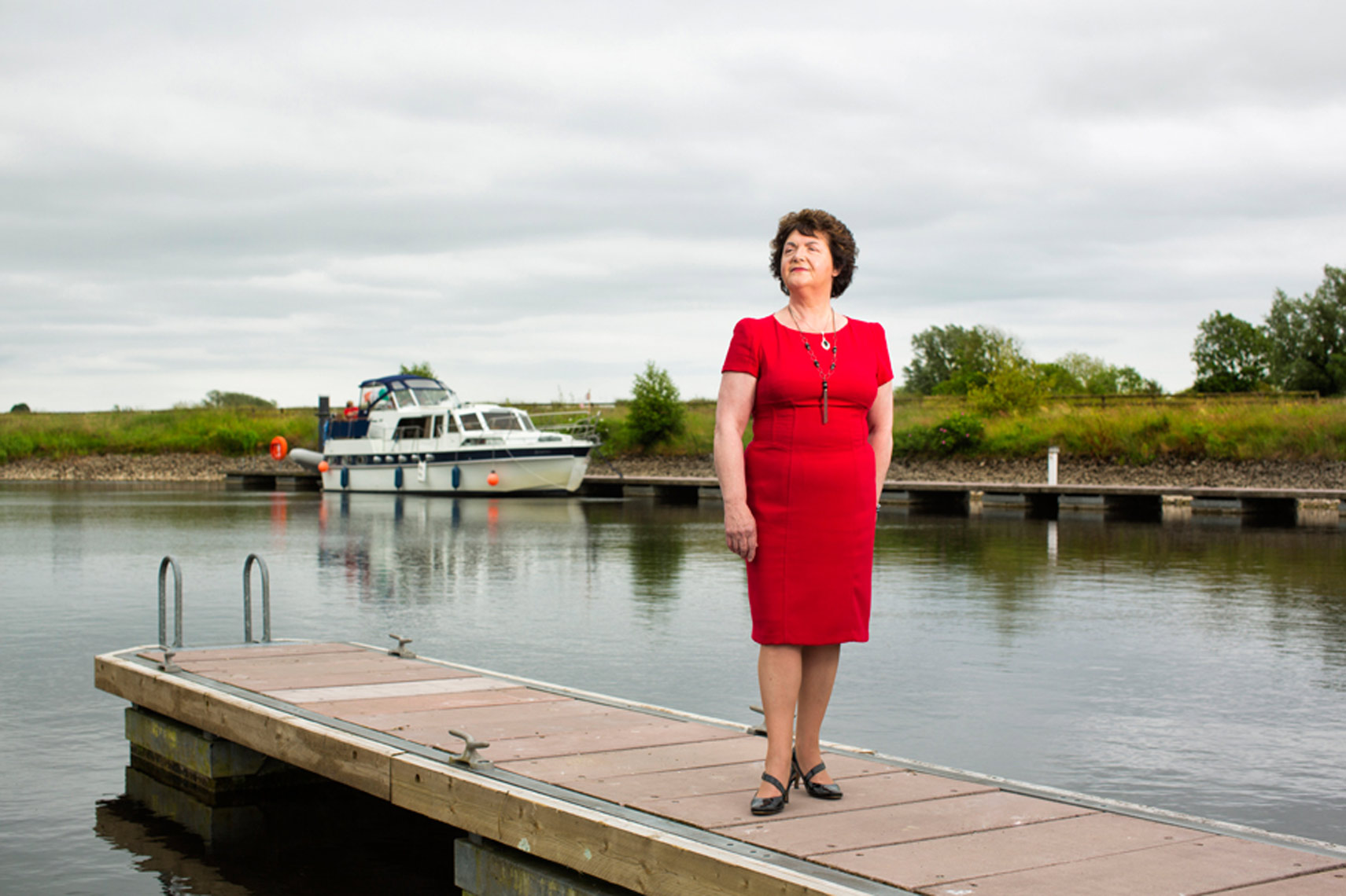 lady with red dress stands by river shannon