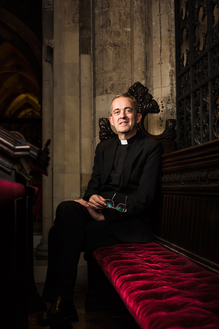 priest sits on red cushion in christchurch cathedral