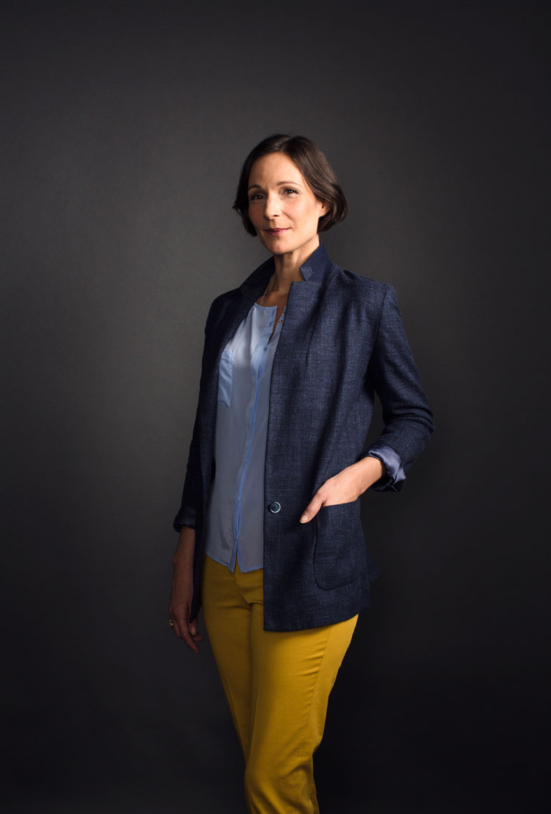 female wearing yellow trousers and blue jacket in front of dark background