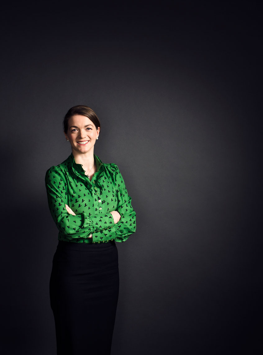 smiling female business executive wearing green top