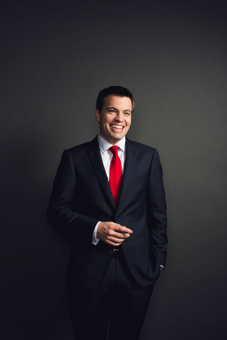 smiling man wearing suit with red tie