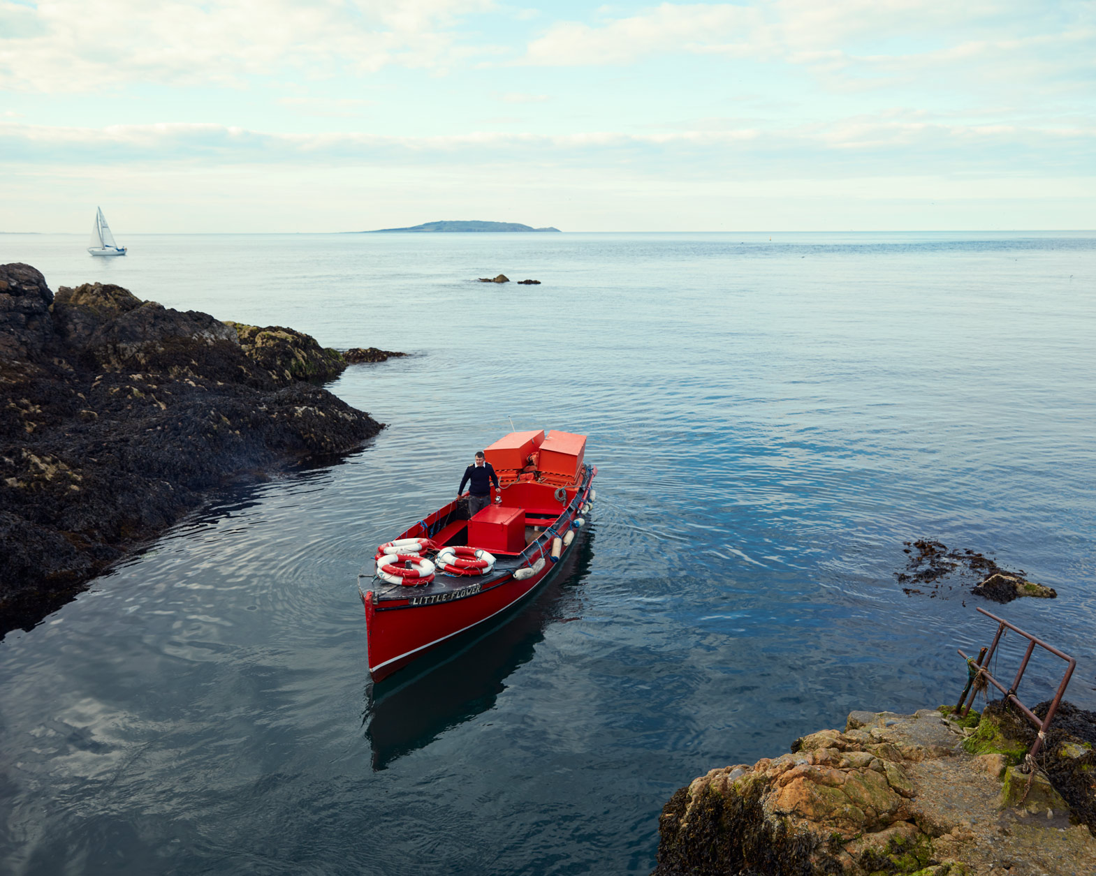 editorial portrait photography of man in red boat