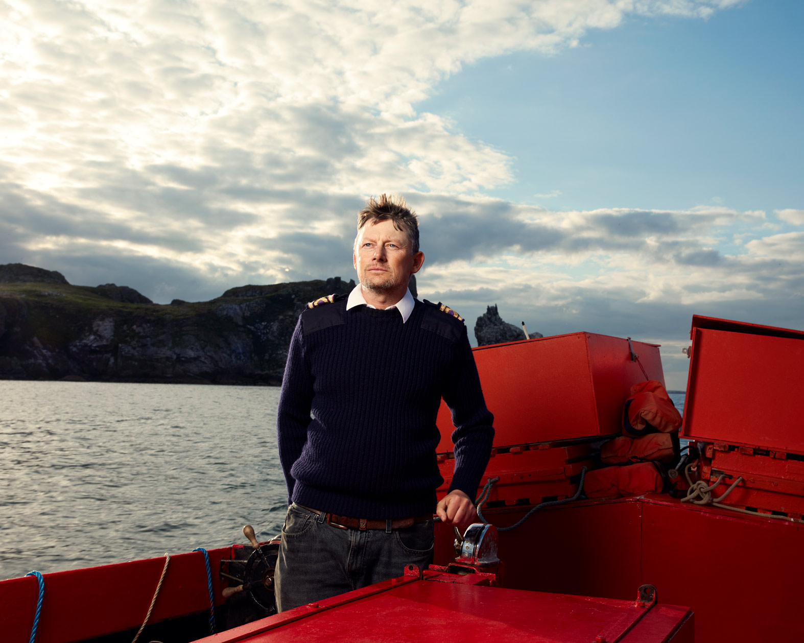 location portrait photography: a  fisherman at controls of  boat
