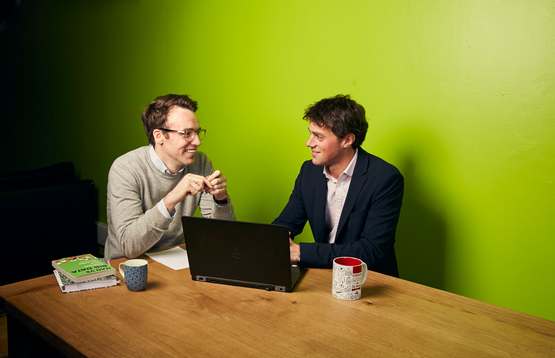 two businessmen chat at table with green backdrop