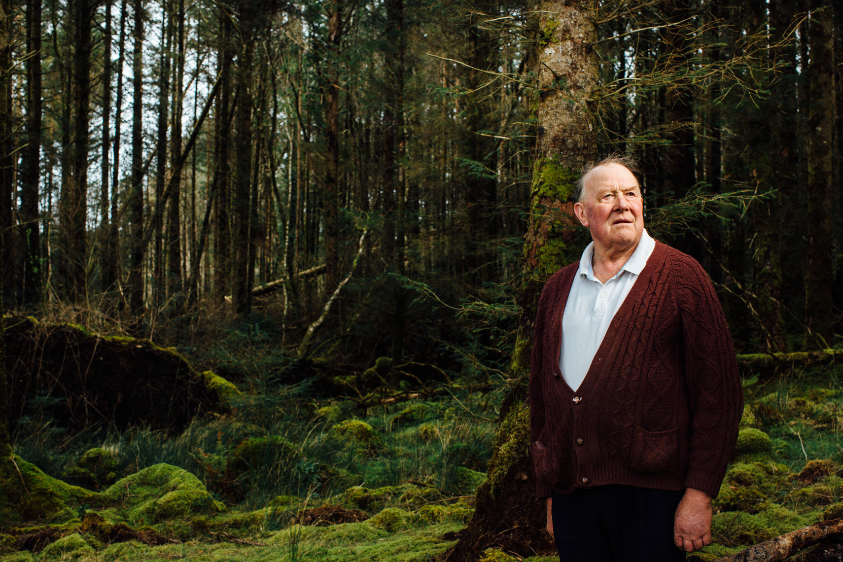 farmer in purple cardigan stands in forest