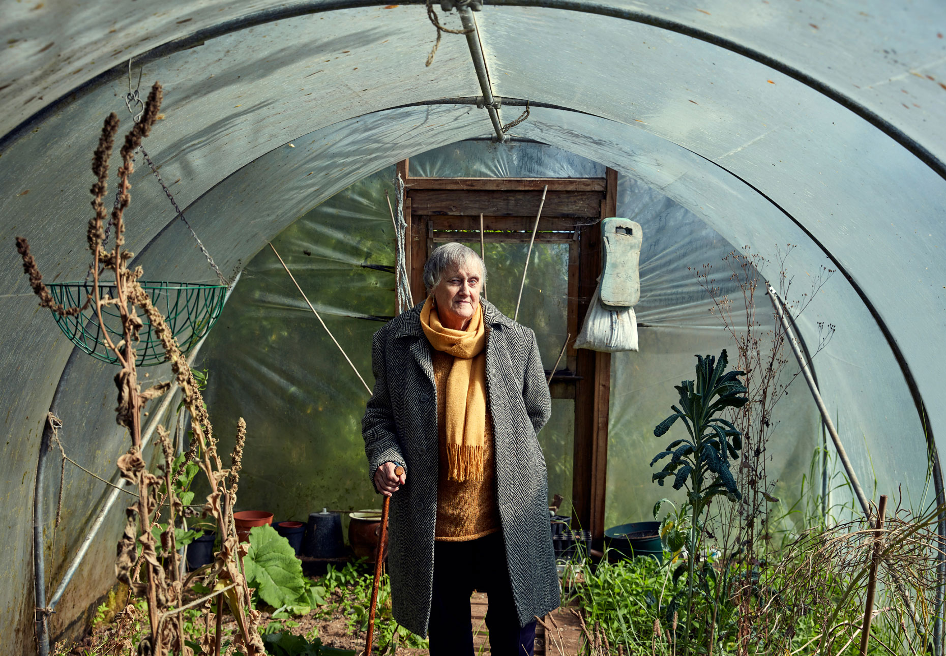 old lady stands in greenhouse with stick