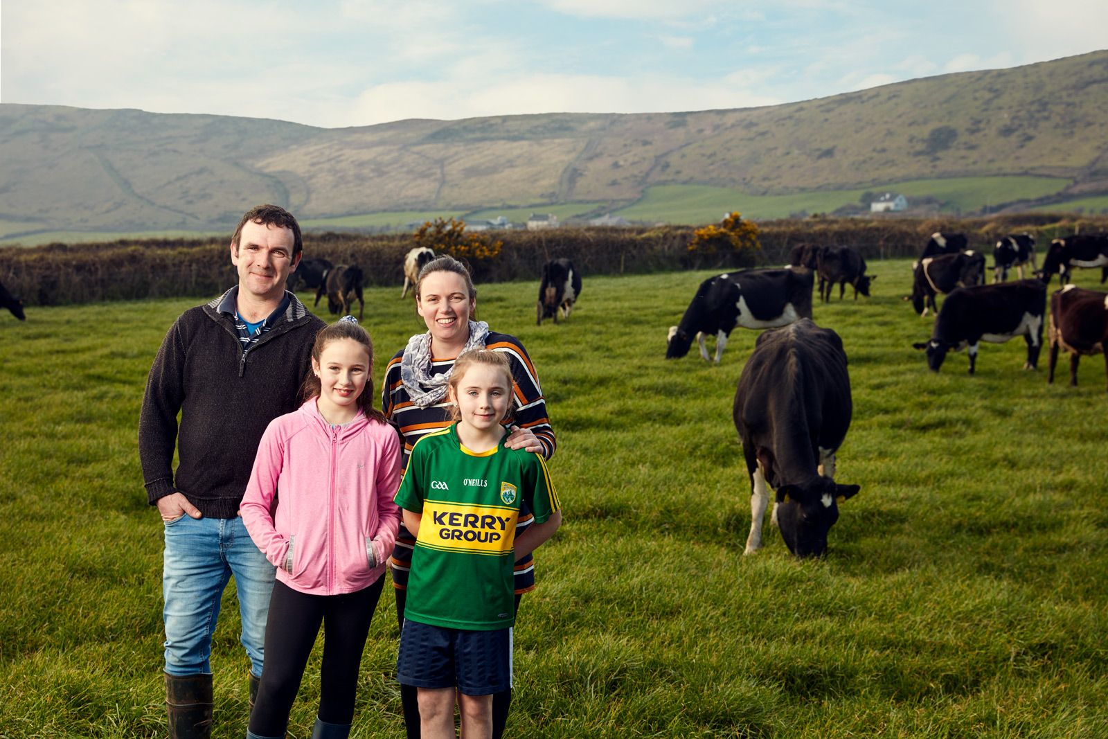 farmer and his family stand in field of cows