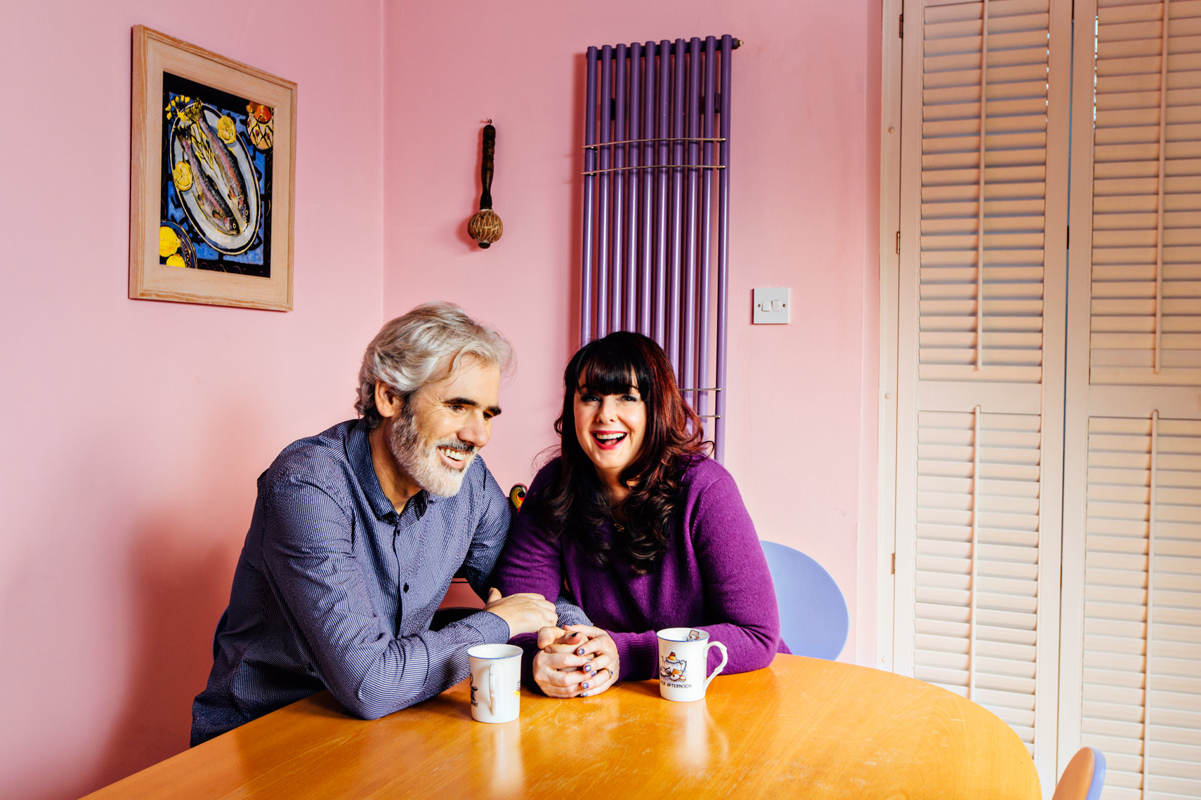 famous author sits with husband in pink kitchen