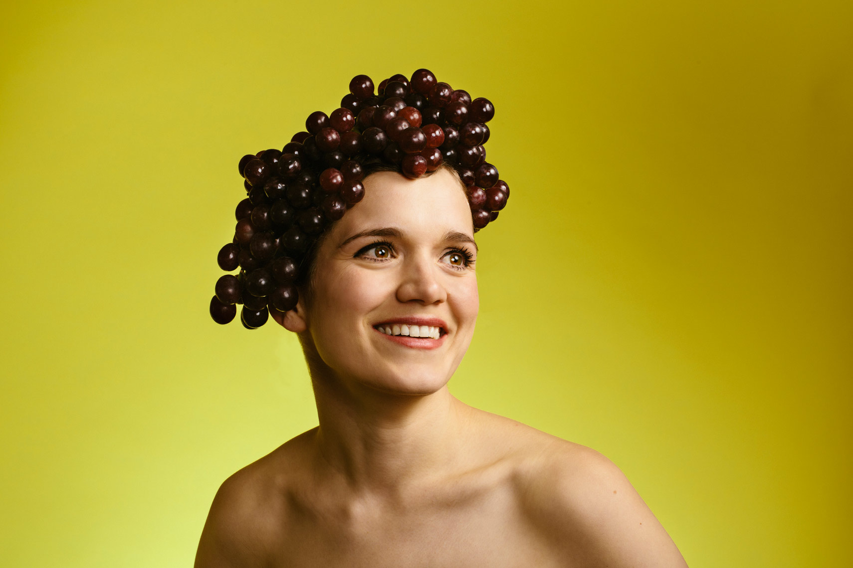 girl wears red grapes on head in front of yellow wall