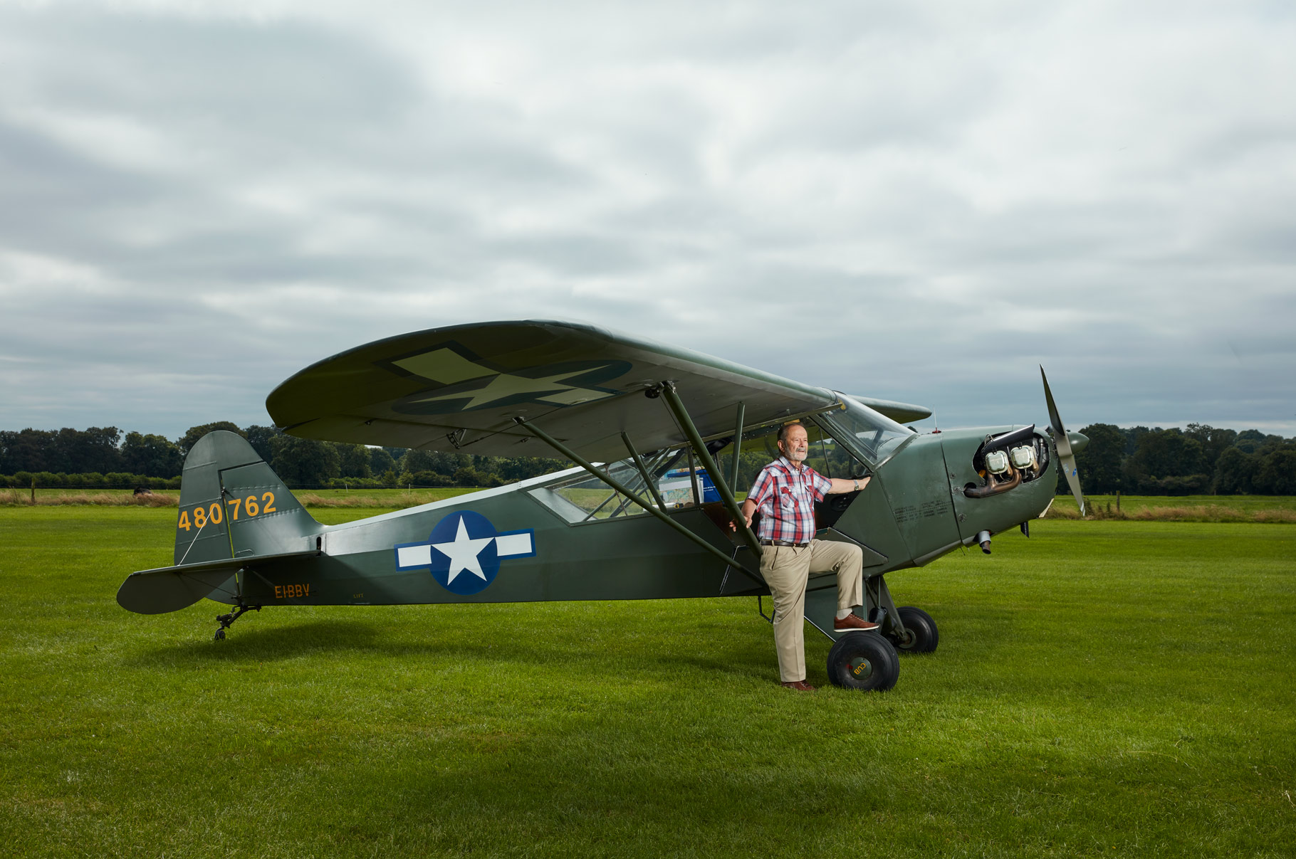 man with L4 grasshopper military aircraft