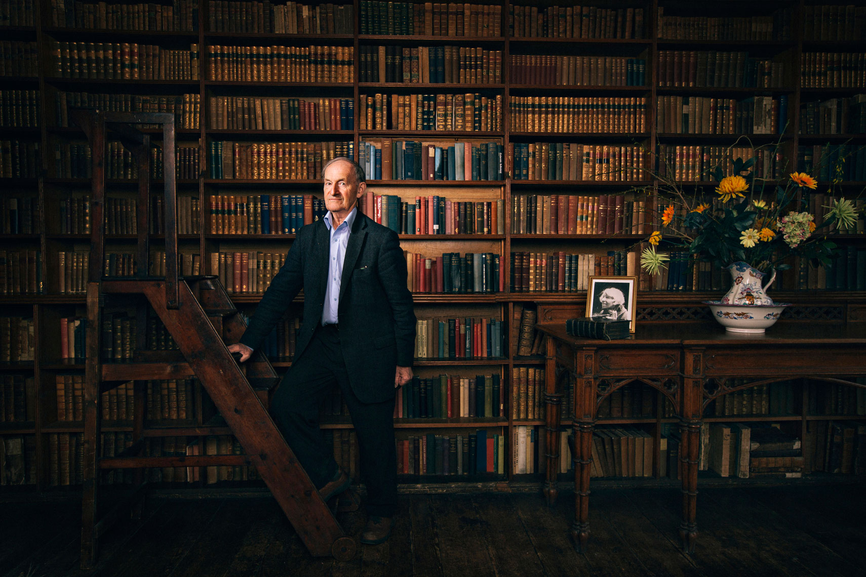 elderly  man stands in front of his library