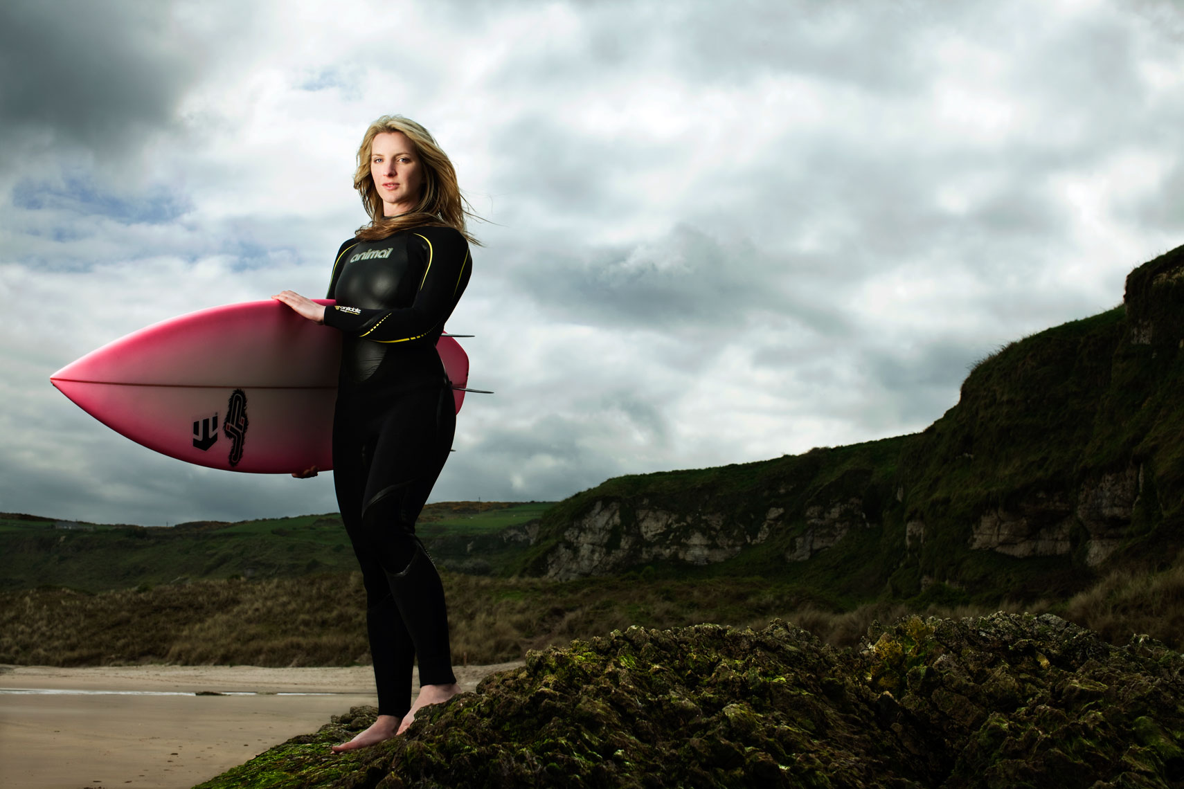 female surfer wearing black wetsuit stands on rock with pink surfboard