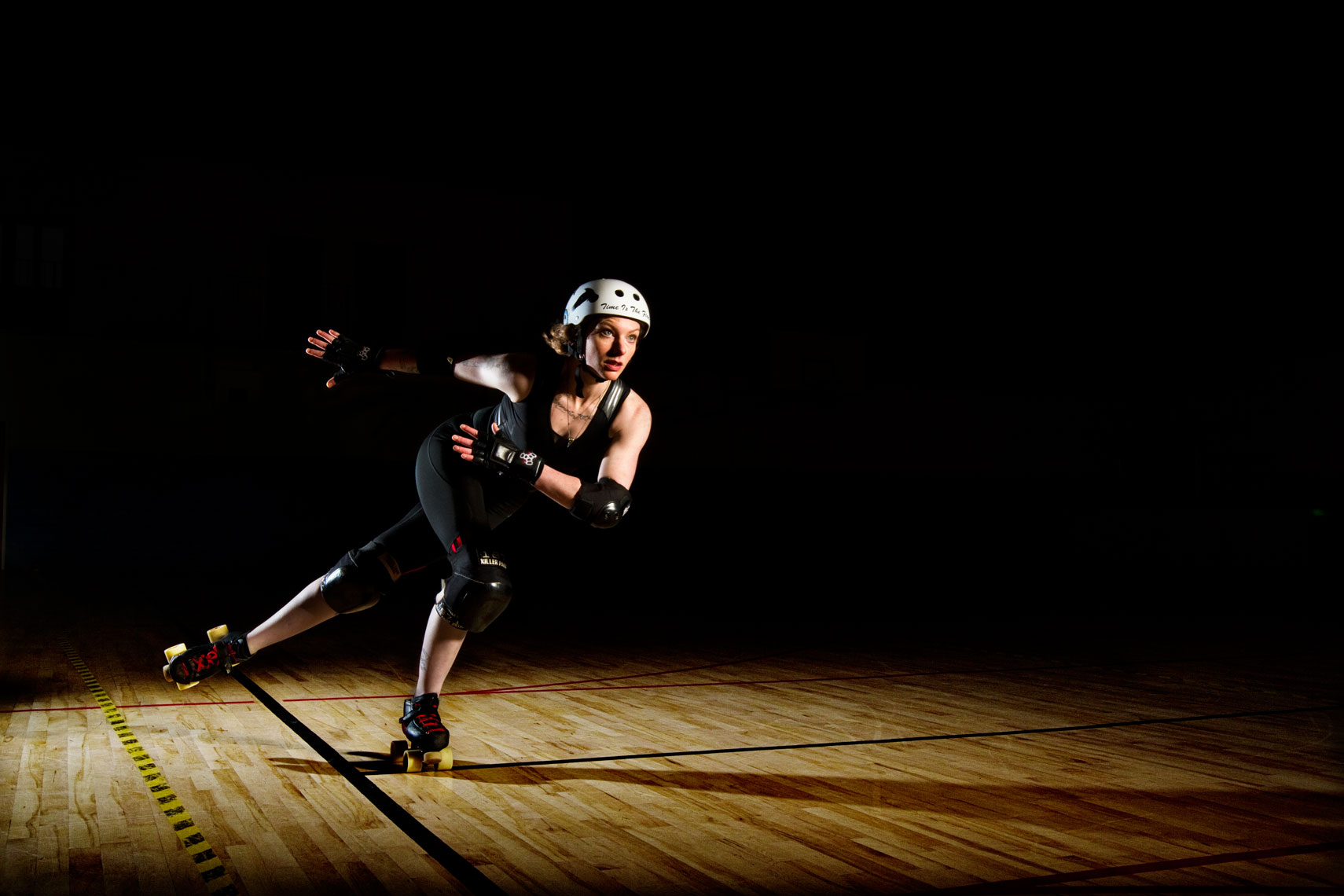 roller derby girl  with helmet and black suit sports photographer