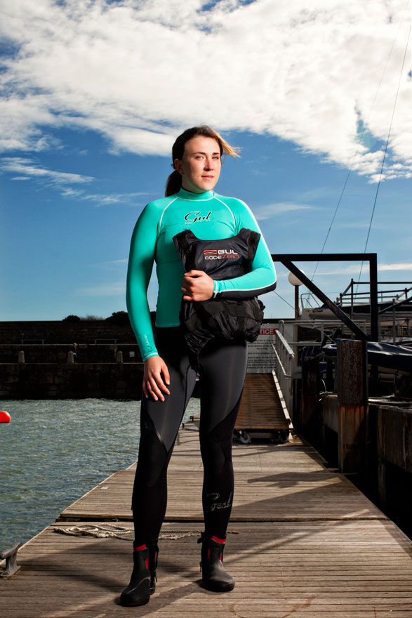 olympic sailor stands on jetty wearing green and black wetsuit holding lifejacket