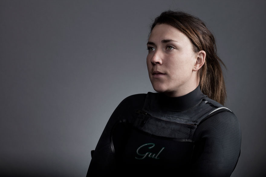 female sailor wearing black wetsuit sits in front of grey wall