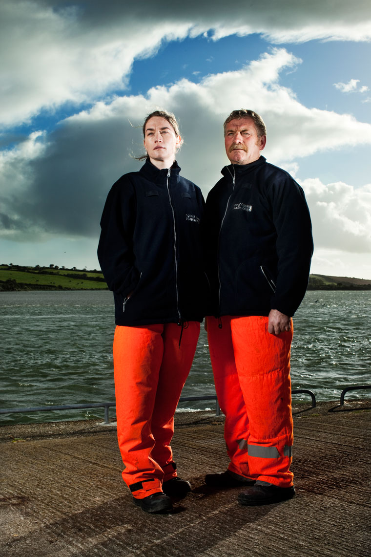 two coast guard members  stand on jetty