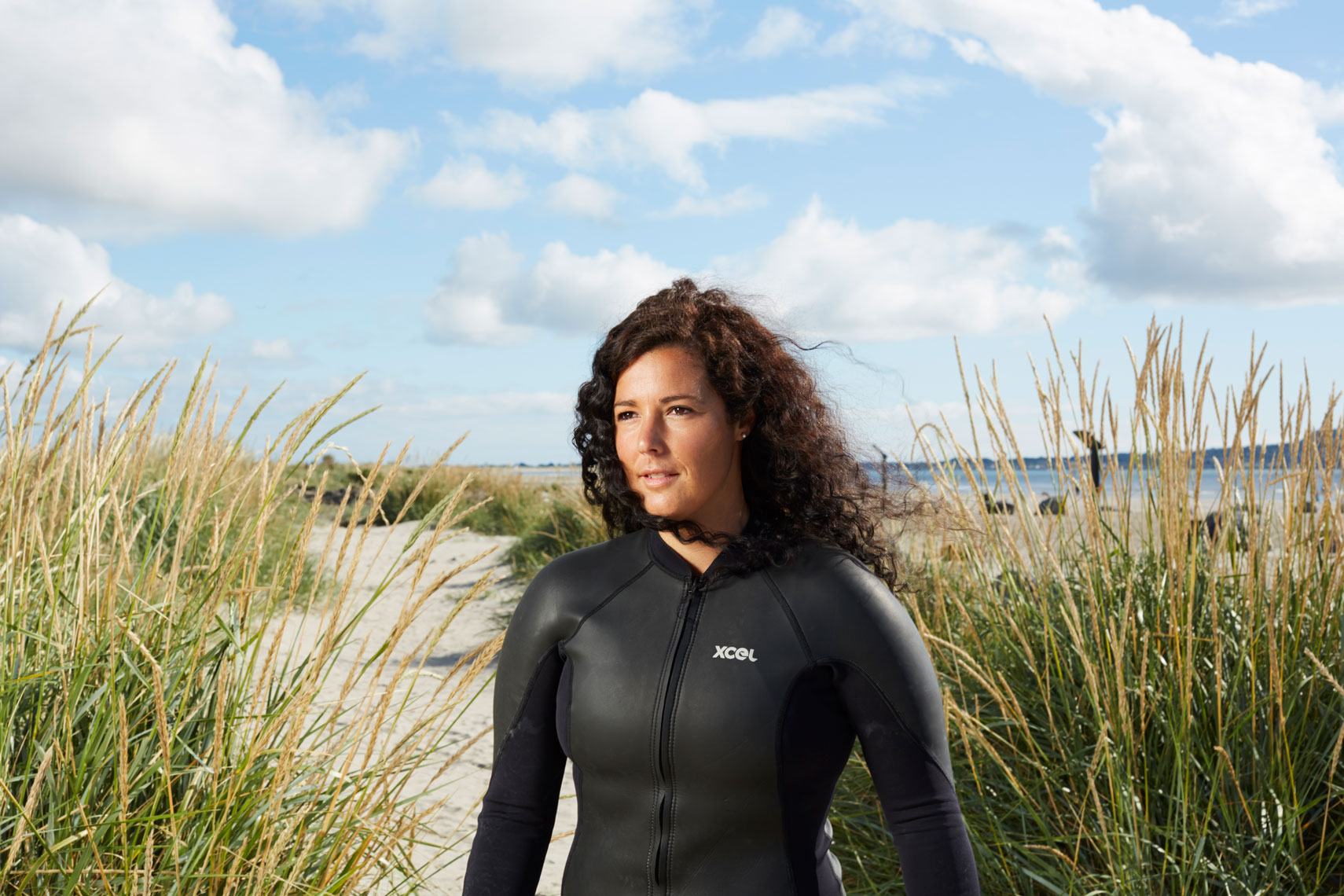 athletic girl wearing wetsuit stands amongst sand dunes