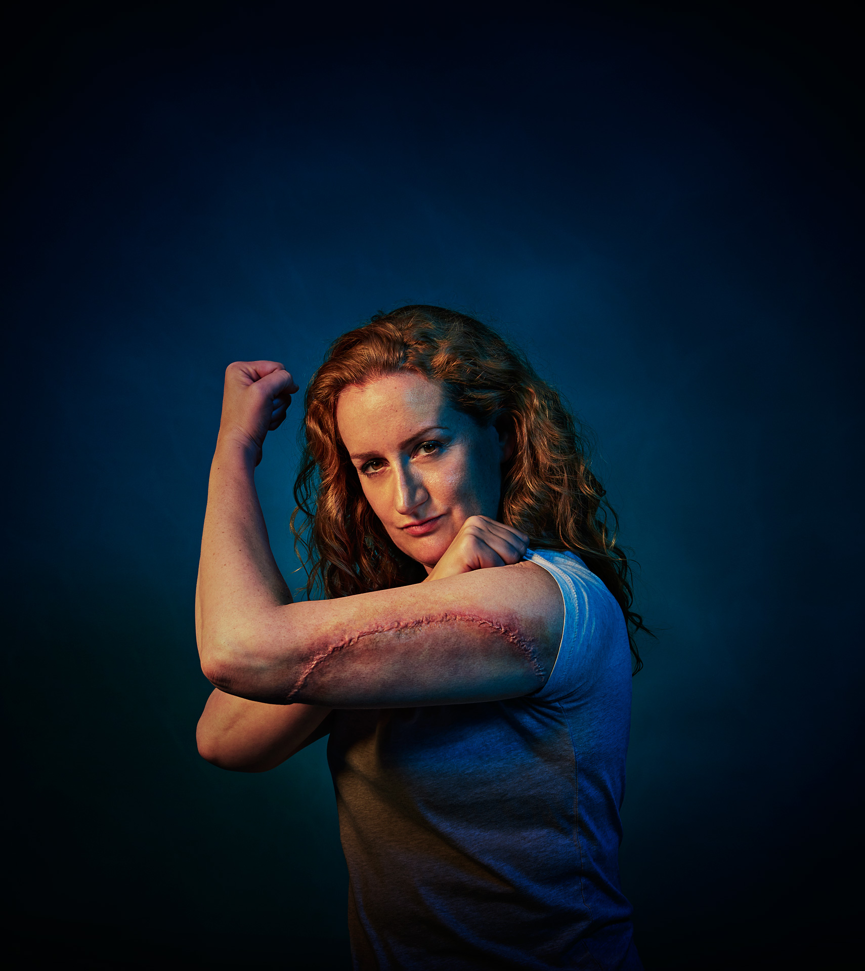 lady with red hair flexes her bicep and shows shark attack