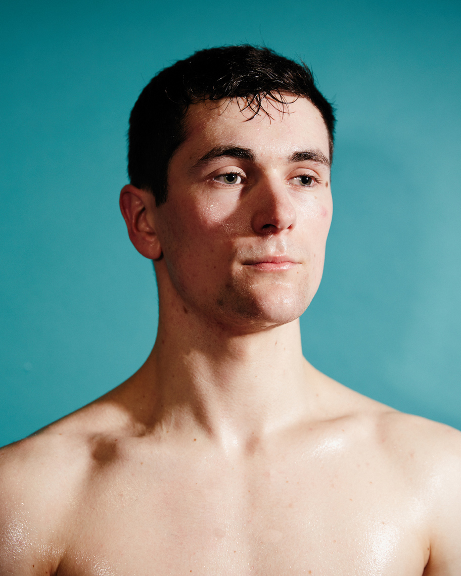 portrait of sweating kickboxer in front of blue backdrop