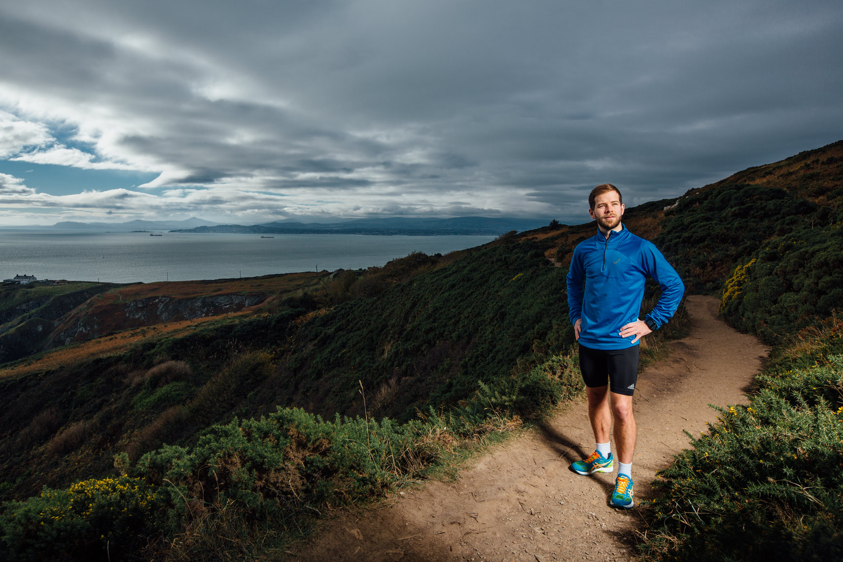 dramatic portrait of runner on cliff walk wearing blue top