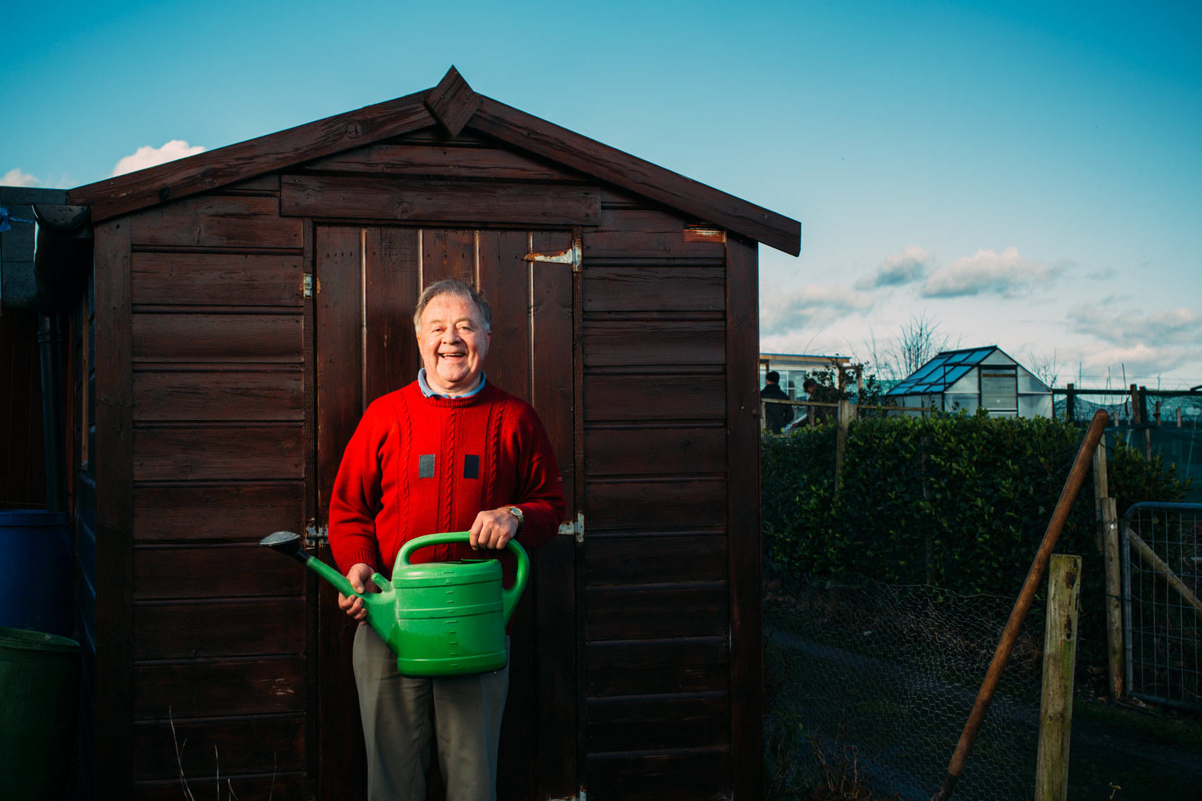 laughing man with red jumper and green watering can stands beside shed
