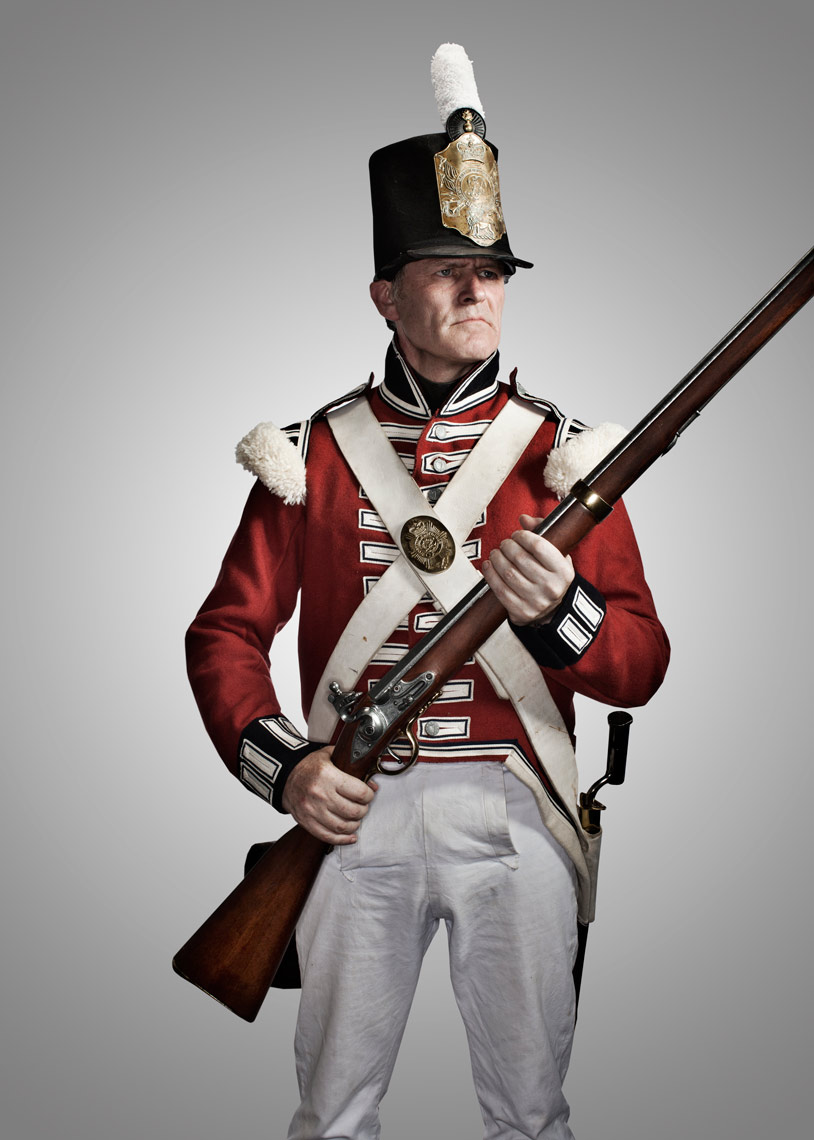battle reenactor in red and white carries gun