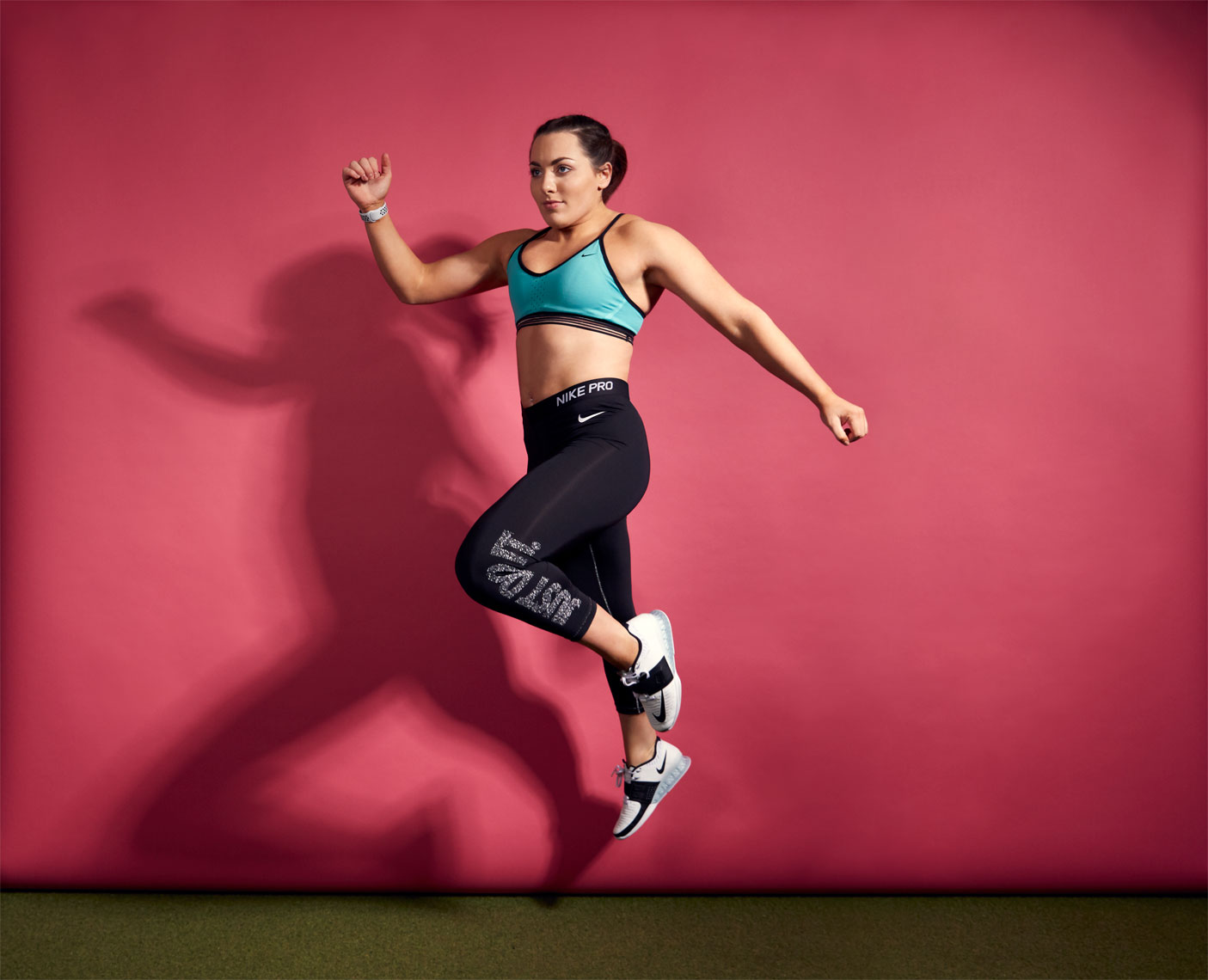 female crossfit athlete jumps against pink wall