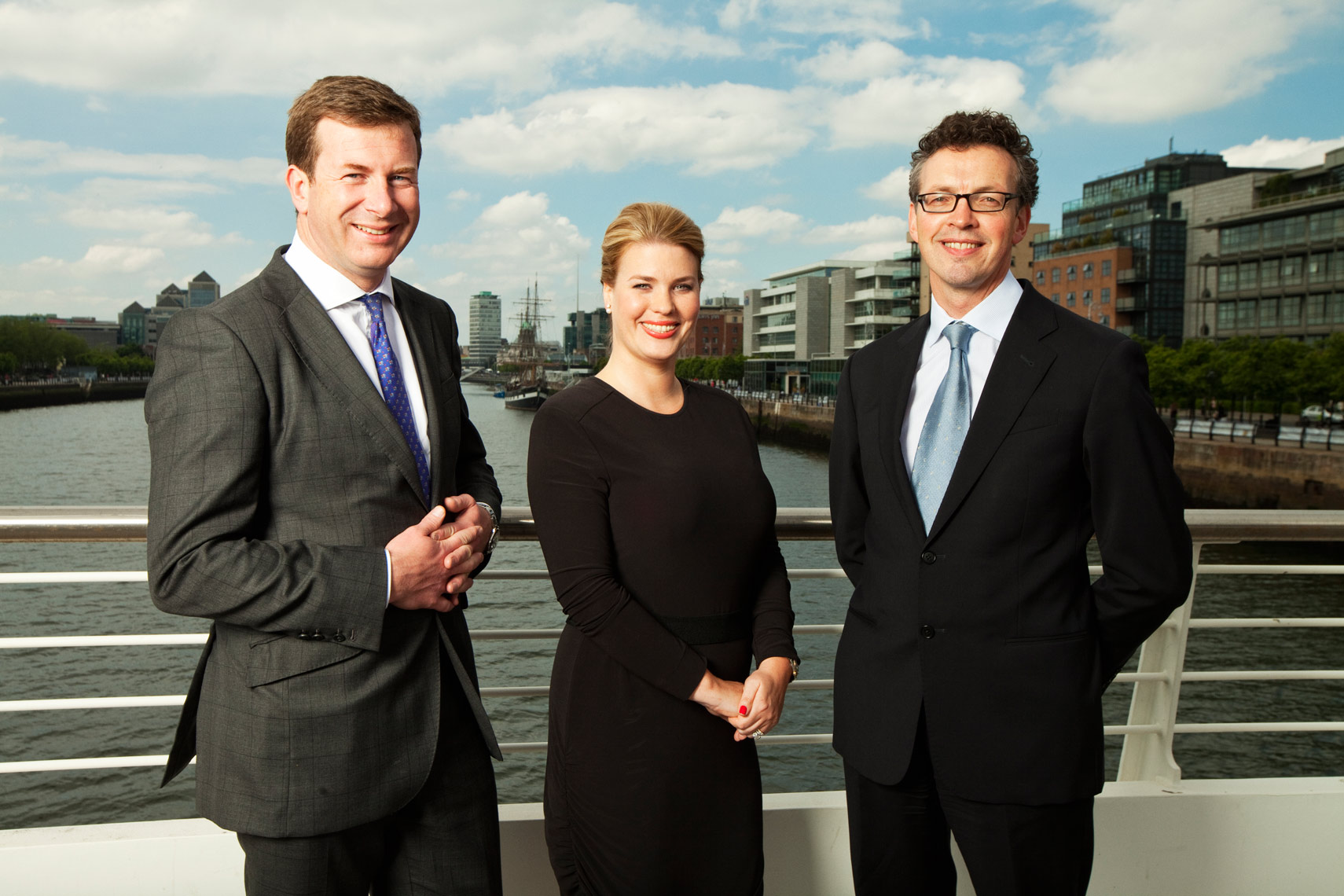 three people in suits stand on city bridge for corporate portrait